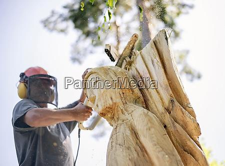 wood carver carving angel sculpture using