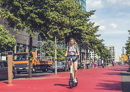 young woman riding e scooter on