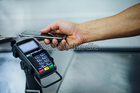 customer paying contactless with his smartphone