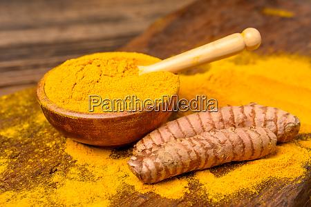 dried curcuma powder in a wooden