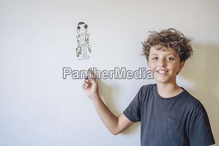 portrait of smiling boy pointing to