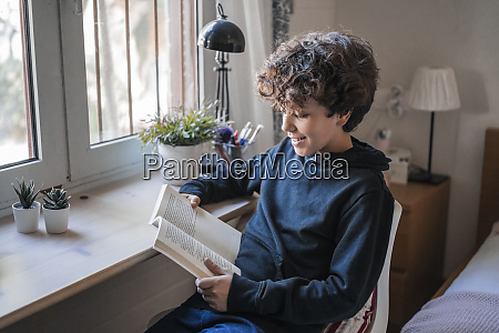 smiling boy reading book at home