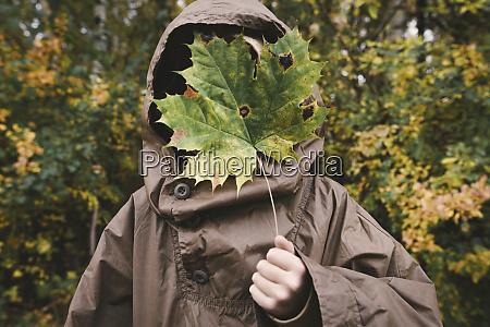 boy wearing brown rain coat hiding