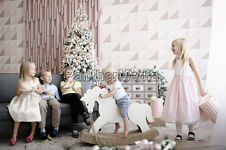 five children playing and eating cookies