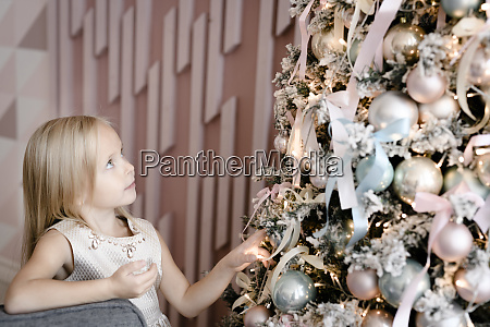 blond little girl watching christmas tree