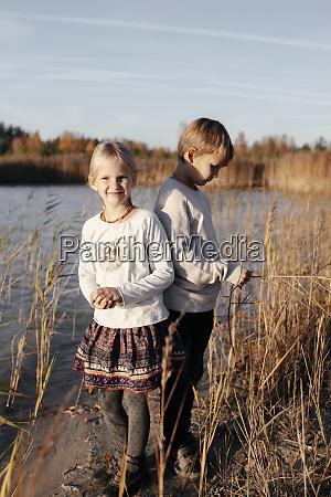 siblings standing at riverside in autumn