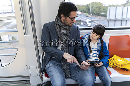 father and daughter in metro and
