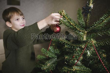 boy decorating christmas tree