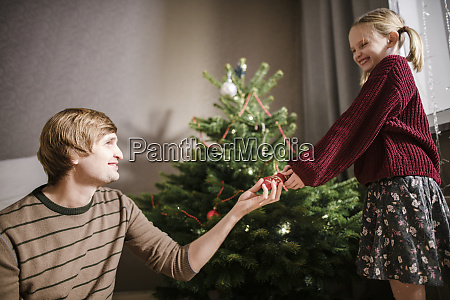 blonde girl with her father decorating