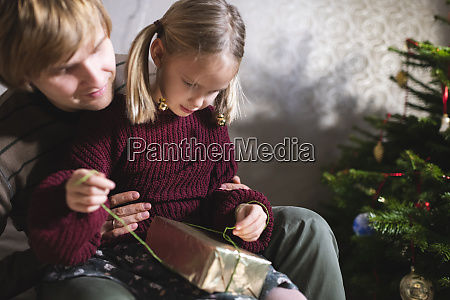 blonde girl sitting on fathers lap
