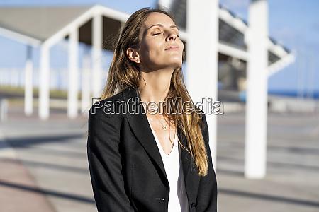 businesswoman standing outdoors enjoying the sunshine