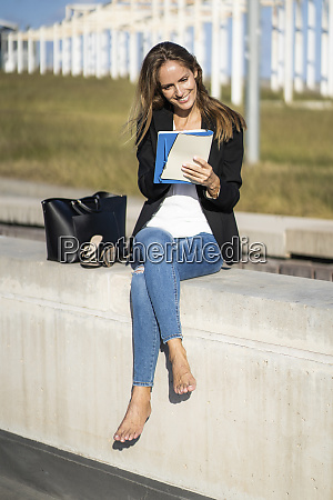 smiling businesswoman sitting on a wall