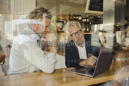 two businessmen with laptop meeting in