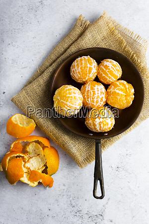 freshly peeled mandarineson frying pan