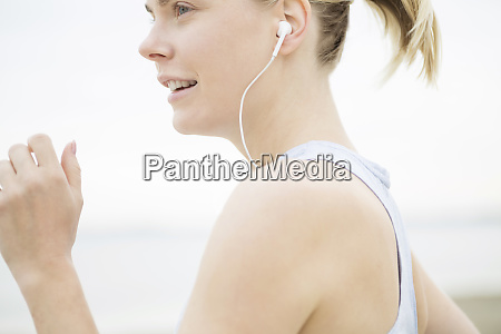 young woman with earphones jogging