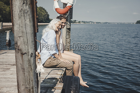 mother and daughter sitting on jetty