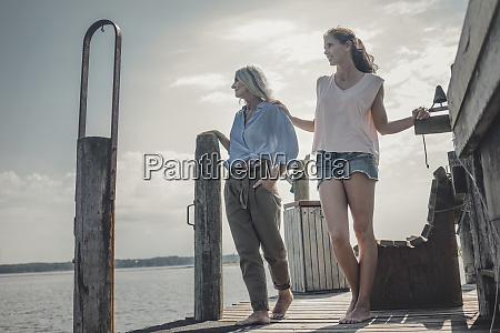 mother and daughter standing on jetty