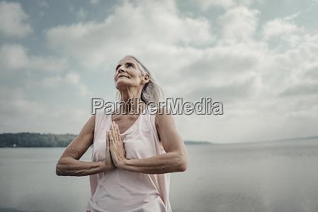senior woman meditation at the sea