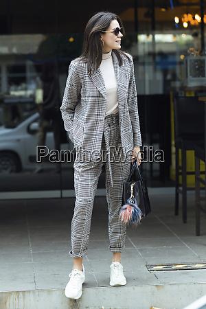 smiling stylish woman standing outside a