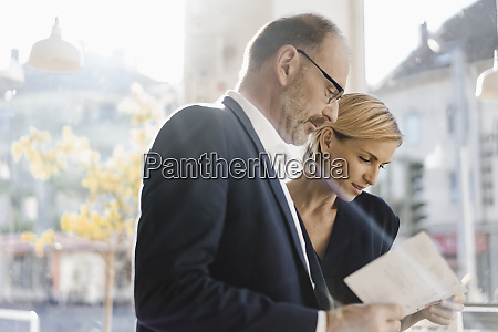 businessman and woman reading menu in