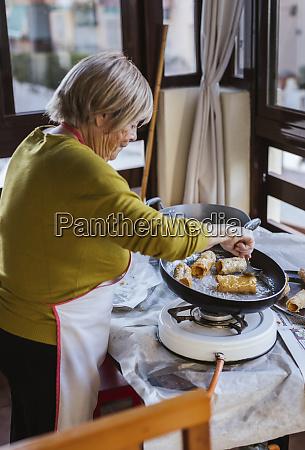 senior woman preparing spanish christmas pastry