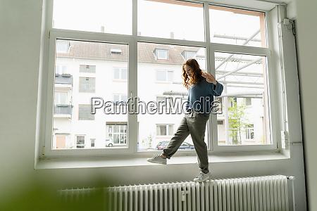 redheaded woman balancing on heater in