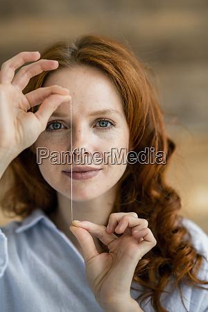 portrait of redheaded woman holding thread