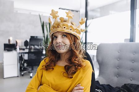 businesswoman in office wearing a crown