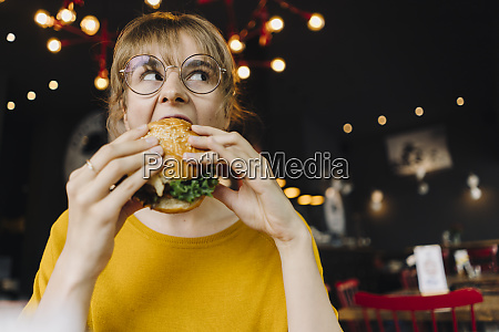 young woman eating burger in a