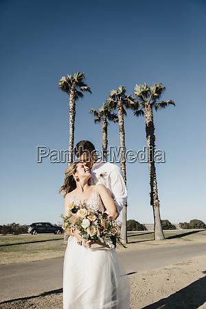 happy bride and groom hugging at