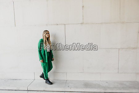 blond young woman wearing green pantsuit