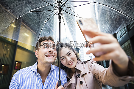 happy couple with umbrella taking a
