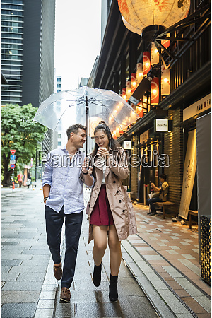 happy couple with umbrella walking in