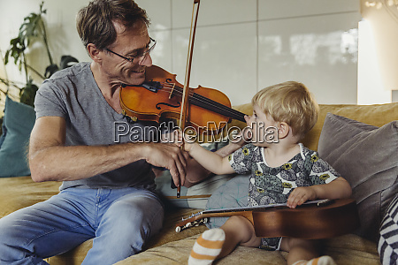 toddler watching his father playing violin