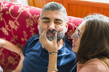 mischievous daughter with father on couch