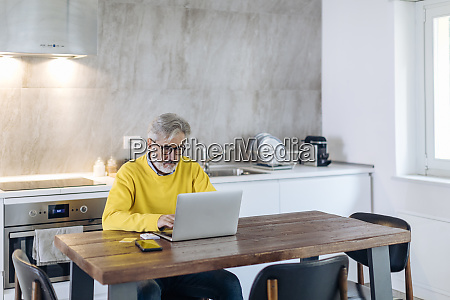 mature man using laptop at table