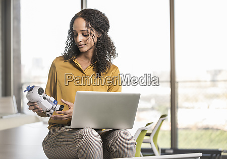 young businesswoman sitting on desk in