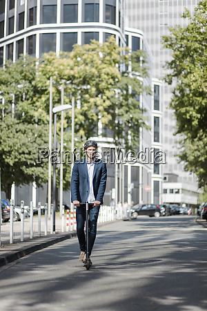 young businessman riding e scooter in