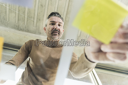 mature businessman working on adhesive notes