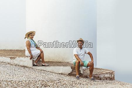 senior tourist couple sitting on steps