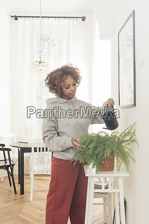 young woman water potted plant at