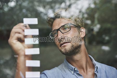 casual young businessman with adhesive notes