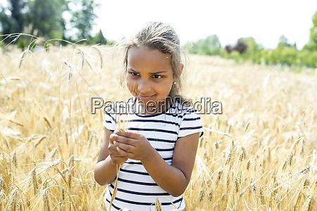 little girl standing in wheat field