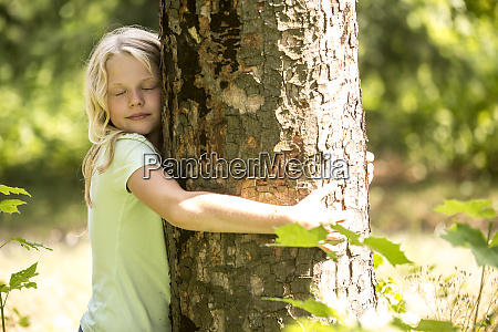 little girl hugging tree in forest