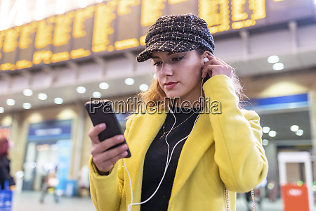 woman at train station checking her