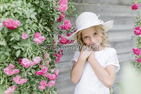 portrait of smiling girl at rosebush
