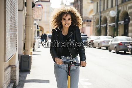 portrait of smiling teenage girl riding
