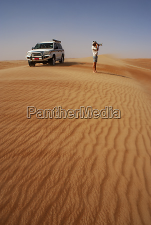 man taking pictures in the desert