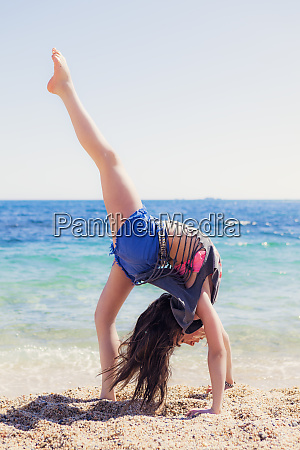 girl doing gymnastics on the beach