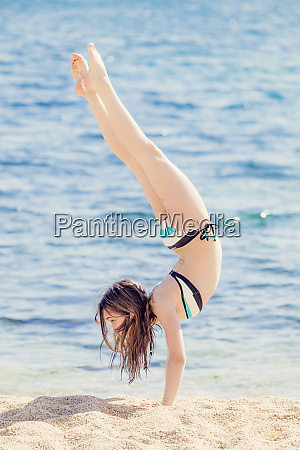 girl practicing handstand on the beach